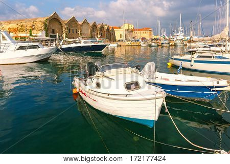 Chania Arsenals, the Venetian shipyards, and fishing boats in old harbour of Chania with Lighthouse in cloudy summer morning, Crete, Greece