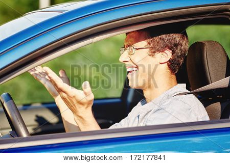 Young annoyed hispanic man wearing glasses and blue jeans shirt, sitting behind wheel of his car and and gesturing with his hands while driving in traffic jam - road rage concept