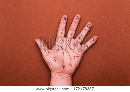 Palm of left hand with drawn symbols of palmistry. Concept of chiromancy