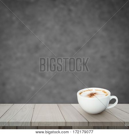 Redolent cappuccino coffee on wooden floor with blurred image of abstract background.