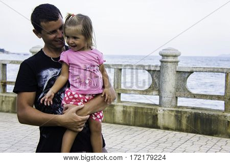 man holding the girl in his arms. They are laughing. Dad and daughter hugging.