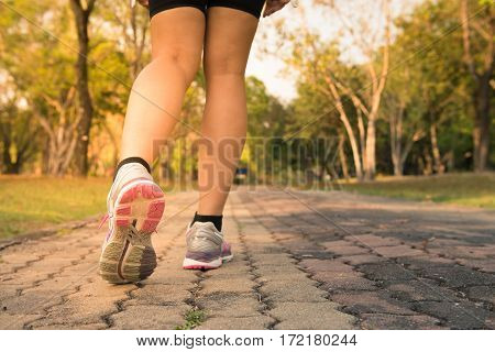 Fitness woman training and jogging in summer park close up on running shoes. Healthy lifestyle and sport concept