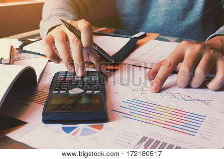 Businessman Using Calculator And Pointing Paper Chart On Desk.