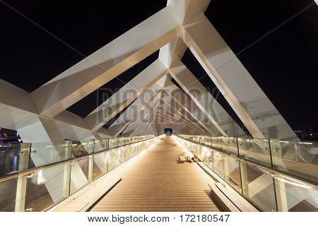 DUBAI UAE - NOV 29 2016: New pedestrian bridge over the Dubai Water Canal illuminated at night. United Arab Emirates Middle East