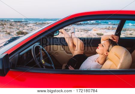 Woman Sitting On The Front Seat Of The Red Ferrari With Legs In The Window