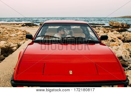 Young Girl In White Dress And Man Kissing On The Front Seats Of The Red Ferrari