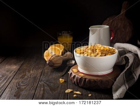 Corn flakes with milk on dark wooden background. Copy space. Healthy breakfast concept.