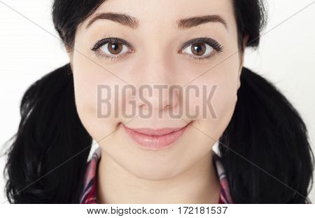 Close up portrait of young girl or woman with black hair tied in two pigtails, she is smiling and friendly looking in the camera