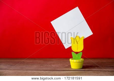 Flowerpot model of note clip on the wood table and red background.