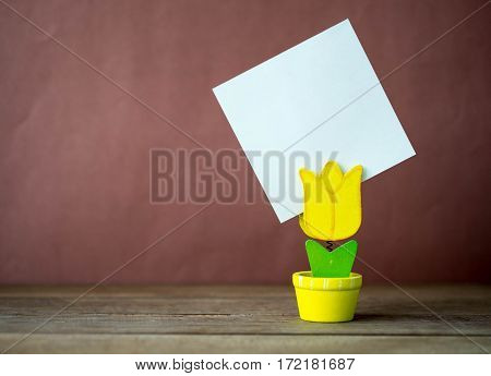 Flowerpot model of note clip on the wood table and red-brown background.