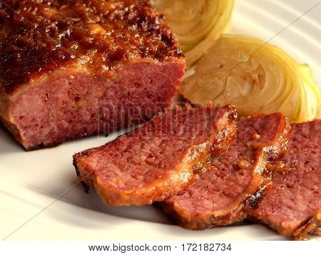 Braised and Glazed Corned Beef with Cabbage: served on a white platter