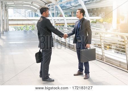Two Businessmen are shaking hands, greeting man