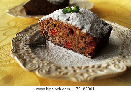 Fruitcake with chocolate and nuts on plate