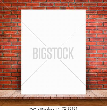 Blank white paper poster lean at brick wall and wood table. For text input or according to your design.