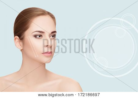 Spa portrait of attractive woman with arrows on her face over blue background. Face lifting concept. Plastic surgery treatment, medicine