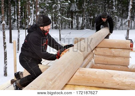 Leningrad Region Russia - February 2 2010: Log Home Construction Handcrafting two workers doing assembly of the wall made of logs.