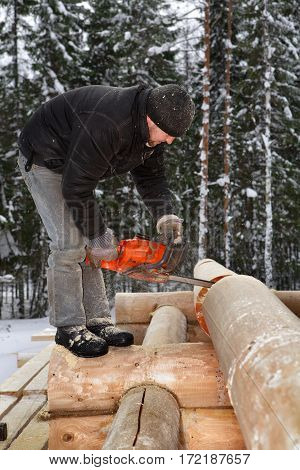 Leningrad Region Russia - February 2 2010: Construction works Man cuts off beam using chainsaw for future log cabin.