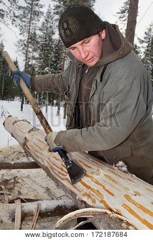 Leningrad Region Russia - February 2 2010: The process of peeling and debarking of wood hand peeling logs with a drawknife.