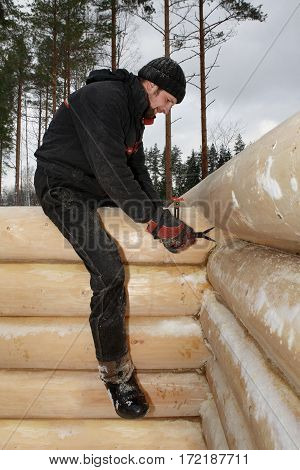 Leningrad Region Russia - February 2 2010: Builder scribing a joint log will also be scribed along it's length so the insulated groove will match the log below and give a good seal.