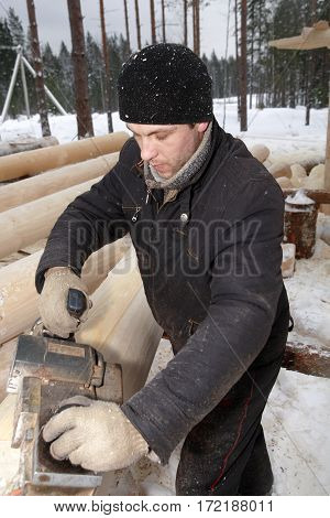 Leningrad Region Russia - February 2 2010: Carpenter sanding a log using an electric planer.