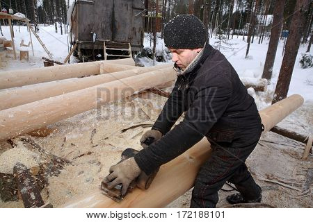 Leningrad Region Russia - February 2 2010: Young man handles a log for building a log house from the planing machine.