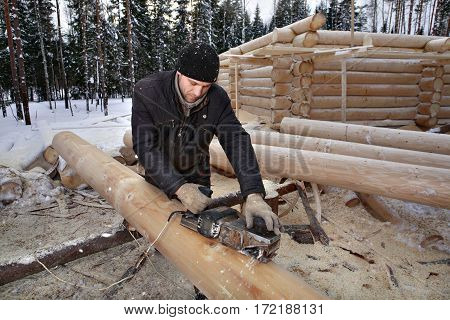 Leningrad Region Russia - February 2 2010: Machining logs for the construction of log home removing the bark using a planing machine.