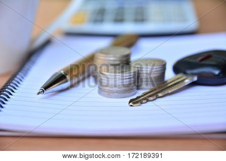 Pen stack coins key of car put on note book and calculator for finance and business
