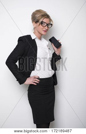 Young beautiful business woman shows on your phone against a white wall