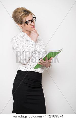 Secretary in the office. Portrait of a beautiful young woman in a white blouse and black skirt on white wall background