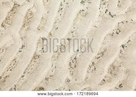 Wavy sand surface with the relief formed by wind gusts.