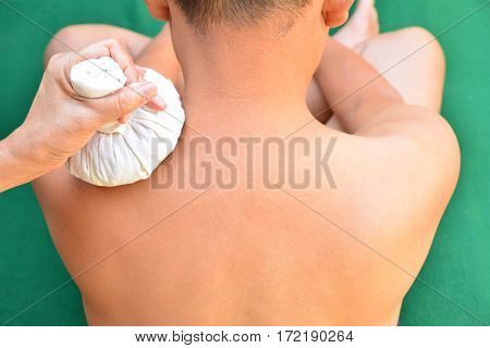 Back neck massage. Massage therapist massaging back neck of a male.