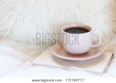 Warm and cozy faux fur furniture with coffee cup and book. Open space for copy.