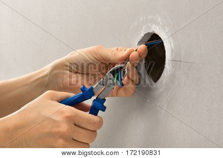 hands of electrician with wire cutter during repair
