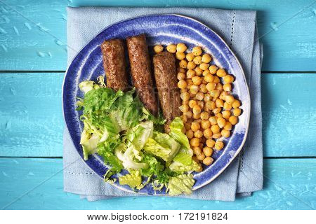 Chevanchichi with lettuce and chick-pea on a plate horizontal