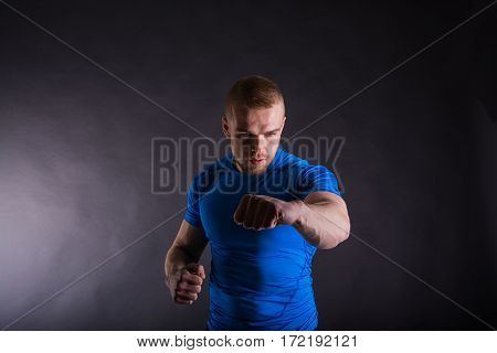 Studio Portrait Of An Aggressive Man In Sports Outfit Punching. View With Copy Space.
