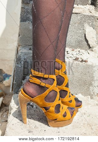 Woman's feet in high heel sandals on the concrete stairs