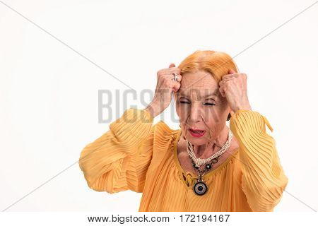 Senior woman with headache isolated. Lady touching her head. Increased intracranial pressure.