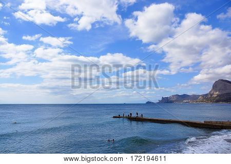 Skyscape. Beautiful clouds in the blue sky over the sea. Fishermen on the pier fishing.