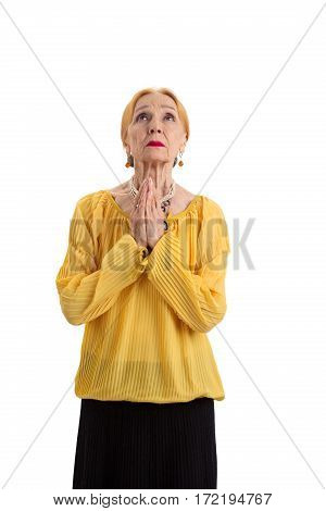 Elderly woman praying isolated. Old lady looking up. Hope for a miracle.
