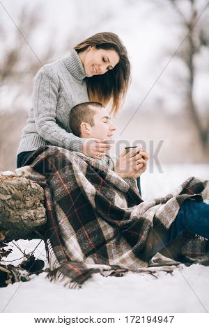 Young Woman And Man Sitting On Tree Trunk In Winter Picnic.