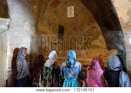 MYRA TURKEY - APRIL 24: The pilgrims are near tomb in church of St. Nicholas on April 24 2014 in Myra Turkey. The Church is on UNESCO's tentative list to become a world heritage site