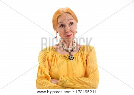 Old woman with arms crossed. Face showing doubt. Read the thoughts.