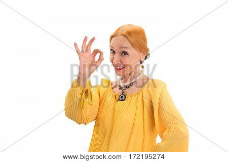 Senior woman showing ok gesture. Smiling female on white background. Success starts from positive thinking.