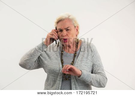 Elderly woman with mobile phone. Serious old lady isolated. Problem must be solved.