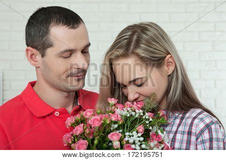 Valentine's day, anniversary, event concept - young woman receives a gift of bouquet of flowers from her boyfriend