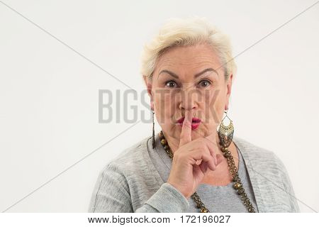 Senior lady showing silence gesture. Woman holding finger on lips. Can you keep a secret.