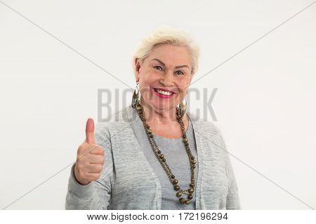 Elderly woman showing thumbs up. Smiling lady on white background. Positive mindset leads to success.