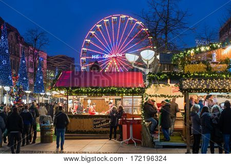 DUISBURG GERMANY - DECEMBER 17 2016: Unknown people at traditional christmas market with illuminated ferris wheel in the center of Duisburg Germany