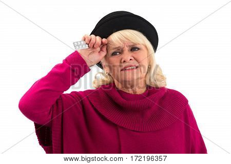 Isolated elderly female with pills. Upset woman touching her head.