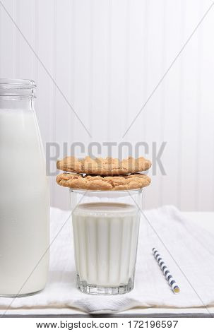 A Milk and Cookie Snack on a white table with white wall. Cookies are stacked on the glass of milk.